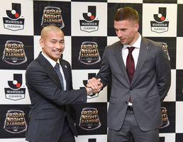 開幕戦の健闘を誓い合い、握手を交わす鳥栖DF吉田(左)と神戸FWポドルスキ=鳥栖市のベストアメニティスタジアム