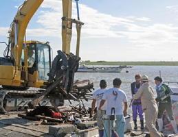 豪雨で流れ着いたごみや流木を回収する漁業者=佐賀市川副町の戸ケ里漁港