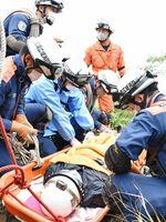 負傷者役の男性(手前左)を担架に乗せる佐賀広域消防局の隊員=唐津市厳木町の天山山頂付近