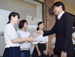 出発式で、田上富久長崎市長から激励を受ける高校生平和大使=13日午後、JR長崎駅前