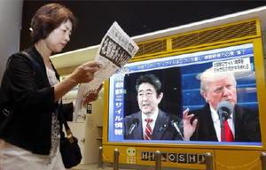 北朝鮮の弾道ミサイル発射を伝える大型モニターの前で新聞の号外を読む女性=29日午前、札幌市