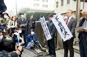 開門を求める請求が棄却され「不当判決」の垂れ幕を掲げる長崎県内の漁業者ら=長崎市内