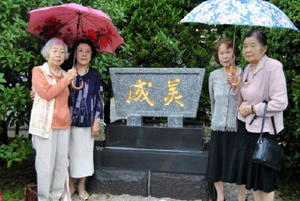 成美高女の記念碑と、移設を計画した「成美会」メンバー=佐賀市の佐賀西高校