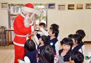 サンタクロースと握手する子どもたち=佐賀市の和泉幼稚園