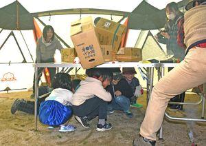 地震を想定した訓練でテーブルの下に避難し、落下物を避ける参加者=上峰町中央公園