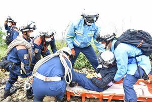負傷者役の男性(中央)を担架に乗せる佐賀広域消防局の隊員=唐津市厳木町の天山山頂付近