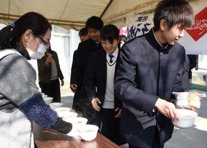 温かいうどんを受け取る生徒たち=神埼市の神埼高