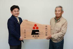 松尾佳昭町長(左)に唐船城築城800年の記念板を手渡す石橋浩さん=有田町役場