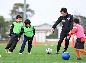 サガン鳥栖のコーチ(右奥)の指導を受ける子どもたち=佐賀市健康運動センター