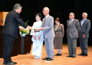 壇上で坂田勝次常務取締役から表彰状を受け取る金婚を迎えた夫婦=神埼市千代田町のはんぎーホール