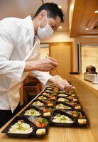医療従事者に届ける弁当に料理を詰めていく平田智隼さん=唐津市の「ひら田」