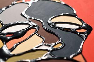 アクリル絵の具で描いた顔を、黒に着色した木工用ボンドで縁取った冨永ボンドさんの作品。単なる黒のアウトラインではなく、独特な光沢と立体感が特徴だ