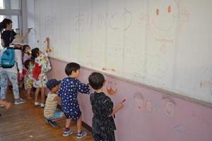 解体される園舎の教室の壁にお別れのメッセージを書き込む園児たち=佐賀市の鍋島幼稚園