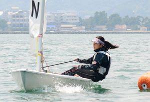 ヨット女子シングルハンダー級第8レース 身を乗り出してヨットを操り、ブイを回る唐津西の鈴木萌風=唐津湾