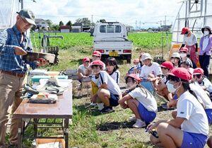 農家の鬼﨑勝則さん(左)の説明に聞き入る児童たち=佐賀市のアスパラガス畑