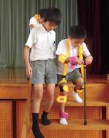 器具を装着し、階段の上り下りを体験する児童
