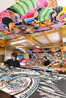 五月のぼりの制作で、生地に色を入れる職人たち=小城市牛津町の城島旗染工