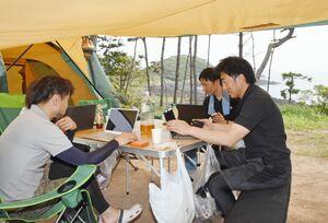自然に囲まれたキャンプ場で、仕事に取り組むANDCOの社員たち=唐津市鎮西町の波戸岬キャンプ場