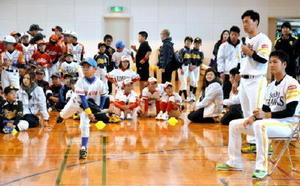 笠原投手(右)や長谷川外野手(右から2人目)からキャッチボールの指導を受ける子どもたち=みやき町の北茂安体育館