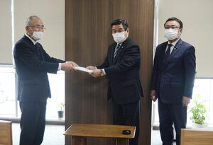 川原田裕明議長(中央)に報告書を手渡した秀島敏行市長(左)=佐賀市の市議会議長室