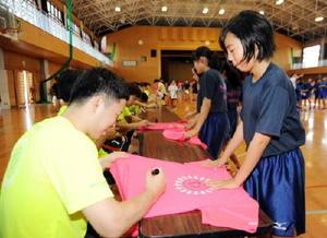 ハンドボール教室で笑顔でサインするトヨタ紡織九州の金東喆選手