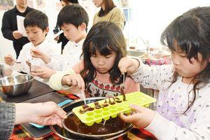 型にチョコを流し込む子どもたち=佐賀市の県国際交流プラザ