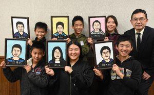 岩崎一男校長(上段右)が切り絵で作った自分の似顔絵を手にする児童たち。作品と対面して「めっちゃ似てる」の声も=唐津市の大志小