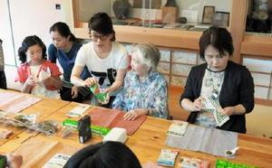 折り紙を折る感覚で、おにぎり作りに挑戦する参加者=佐賀市松原の肥前通仙亭