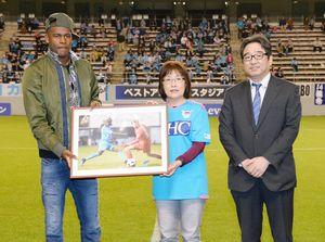 月間MVPに選ばれたイバルボ選手に記念パネルを手渡した松尾牧子さんと佐賀新聞社の大隈知彦編集局長