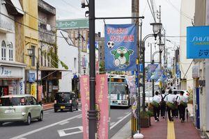 空き店舗がほとんどないJR鳥栖駅前の本通筋商店街沿いの街灯には、「がんばれ!サガン鳥栖」の旗(写真中央)が掲げられている