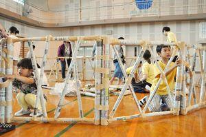 棒状に丸めた新聞紙をガムテープで留め、壁を作る児童ら=佐賀市の開成小