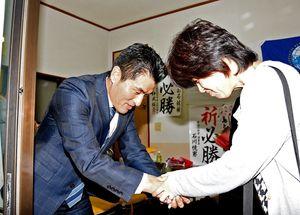支援してくれた人たちと握手を交わす中島徹さん(左)=午後9時9分、佐賀市水ケ江の事務所