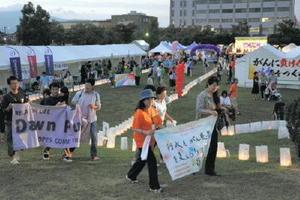 火をともした灯籠の周りで横断幕を持ち、闘病者への支援などを訴えた参加者=昨年9月、佐賀市のどん3の森
