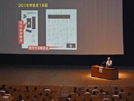 人権教育関係者の研修会の一場面。スクリーンに映っているのは昨年8月、被差別部落出身者の職場に届けられた手紙の画像=佐賀市文化会館