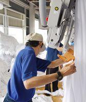障害者42人が就労している山王福祉工場。シーツを機械に投入する利用者たち=佐賀市大和町