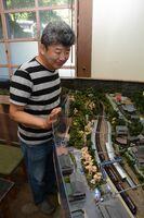 鉄道模型が走る有田の街のジオラマを完成させた辻聡彦代表。ジオラマはJR上有田駅周辺=有田町中樽の駅カフェSARAYAMA