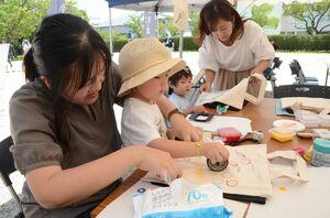 さまざまな形をした工具や部品に絵の具を付け、エコバッグにスタンプする子どもたち=佐賀市の佐賀城本丸歴史館