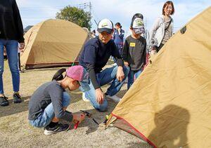 テントを設営する参加者=神埼市神埼町の長崎街道門前広場(提供)