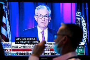 ニューヨーク証券取引所にあるモニターに映し出された記者会見する米連邦準備制度理事会(FRB)のパウエル議長=22日(ロイター=共同)