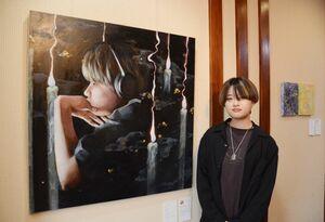 松尾明日香さんと油彩画「この夜に乞う」(910センチ×910センチ)=佐賀市のトネリコカフェ