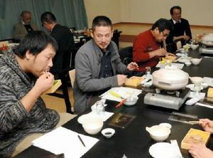 「常磐軒」のかしわ弁当がベースの試作品を試食する町駅弁研究会のメンバーら=江北町の「枡屋」