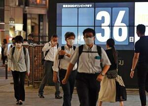 東京五輪開幕までの日数を示すカウントダウンボードを背に、マスクを着用して歩く人たち=17日夜、東京・JR新橋駅前