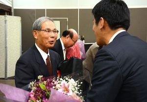 教え子に花束と記念品を手渡される田中公士さん=佐賀市のマリターレ創世