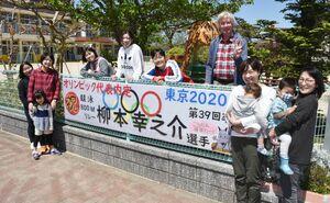 柳本幸之介選手の五輪代表入りを祝う看板を掲げた伊万里カトリック幼稚園の職員=伊万里市二里町