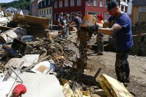 ドイツ西部ノルトライン・ウェストファーレン州の洪水被災地で、片付けを手伝う人々=21日(ロイター=共同)
