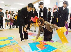 日韓の生徒たちが身ぶり手ぶりで考えを伝え合い、ブロックの位置や向きを検討