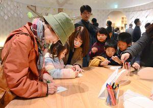 葉の形をしたカードに、維新博の感想や抱負をつづる来場者たち=佐賀市城内の幕末維新記念館