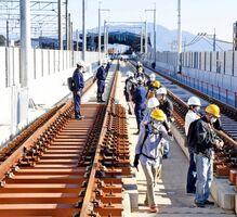 JR武雄温泉駅西側の新幹線の工事現場を歩くJR九州ウォーキングの参加者=武雄市武雄町