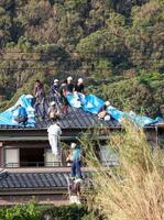 台風15号の被害にあった住宅で、屋根にブルーシートなどを張る作業をする地元建設業者やボランティアの人たち=14日午後、千葉県館山市