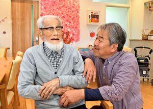 明治から生きる志岐鐵雄さん(左)と孫の善隆さん=神埼市神埼町鶴のグループホームきぼう